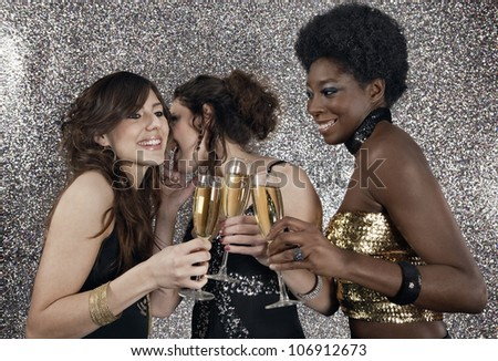 Three girls toasting with champagne at a party with a silver glitter background. - stock photo