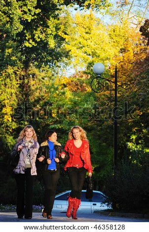 Three girls walk on park. They talk and smile - stock photo