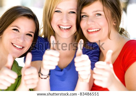 Three girls with thumbs up - stock photo