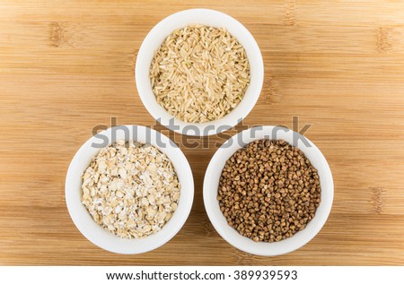 Three glass bowls with oats, buckwheat and brown rice on wooden table - stock photo