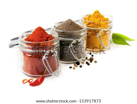 Three glass containers filled with ground culinary spices with chilli peppers, black peppercorns and curry powder on a white background - stock photo