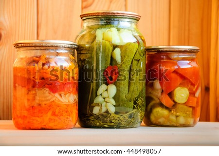 Three glass jars with different home-made pickles prepared for winter storage - stock photo