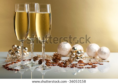 three glasses of champagne, christmas balls and ornaments in front of golden background - stock photo