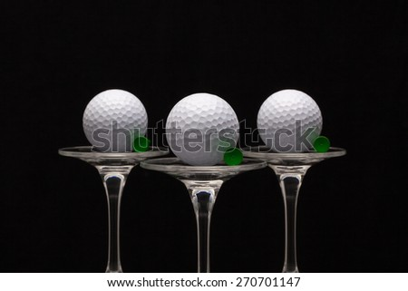 Three glasses of champagne with golf balls - stock photo