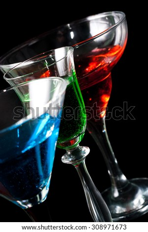Three glasses of different alcoholic beverages on a black background close up - stock photo