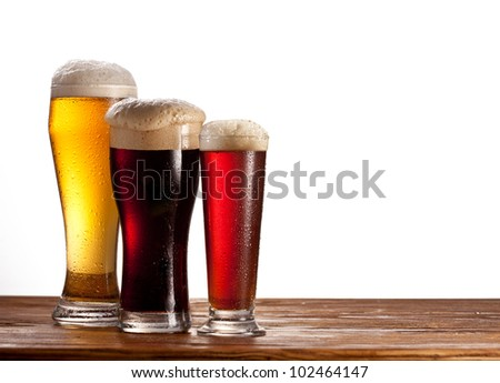 Three glasses of different beers on a wooden table. Isolated on white. - stock photo