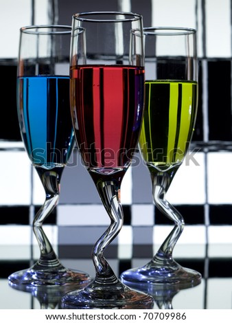 Three glasses on alcohol on black and white background - stock photo