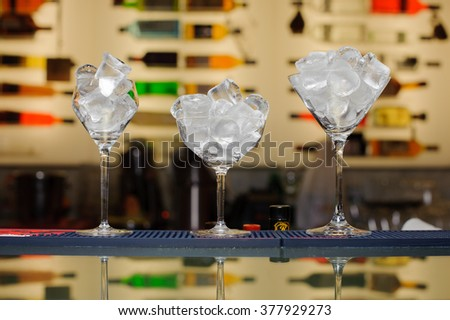 three glasses with ice on the bar bottles on background  - stock photo
