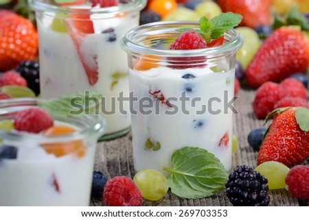 Three glasses with plain yogurt and fresh fruit on a wooden table  - stock photo