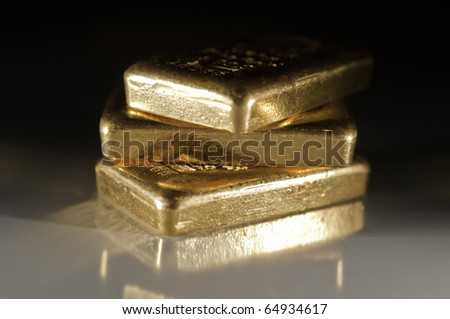 three gold ingots on a dark grey background. shallow depth of field. - stock photo