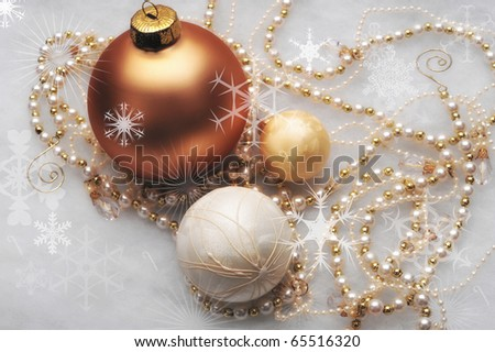 Three gold ornaments with beaded garland surrounding the trio - stock photo