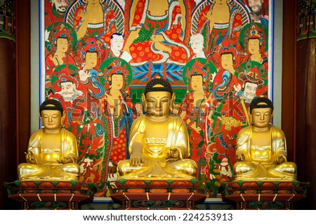 Three golden Buddhas seated in the lotus position at Bongeunsa Temple in Seoul, South Korea. - stock photo