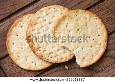 Three golden cheese crackers on dark wood. - stock photo