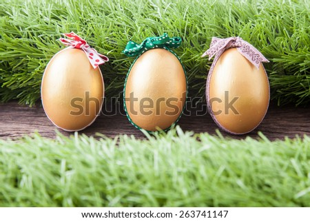 three golden easter eggs with colorful bow laying on wooden tabletop decorated with green grass - stock photo
