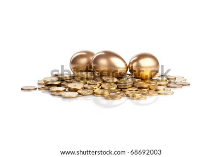 Three golden eggs on coins isolated on white - stock photo