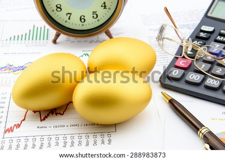 Three golden eggs with a clock, eye glasses, a calculator and a pen on business and financial summary reports. A long term sustainable growth investment concept. - stock photo