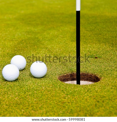 Three golf balls on green with a hole. Shallow depth of field. Focus on the hole and the closest balls. - stock photo