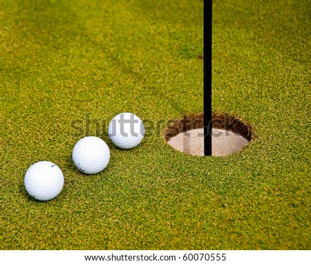 Three golf balls on green with flag. Shallow depth of field. Focus on the closest balls. - stock photo