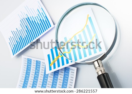 Three graphs and magnifying glass on gray background.  - stock photo