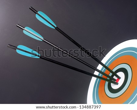 Three Green and Black Archery Arrows Hit Round Multi Colored Target Bullseye Center - stock photo
