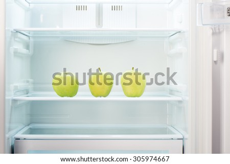 Three green apples on shelf of open empty refrigerator. Weight loss diet concept. - stock photo