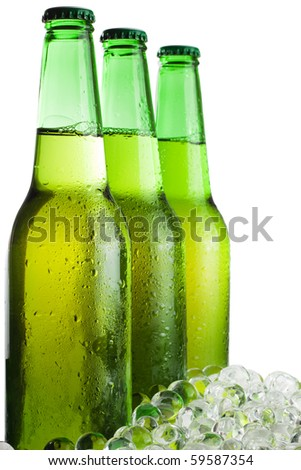 three green beer bottles with ice isolated over white background - stock photo