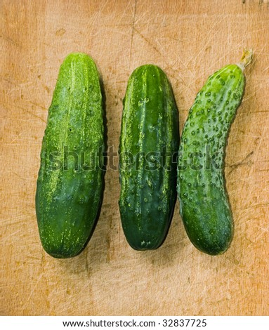 three green cucumber on wood table with selective focus - stock photo