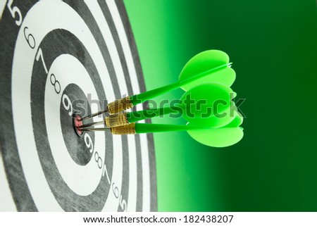 Three green darts pinned right on the center of dartboard - stock photo
