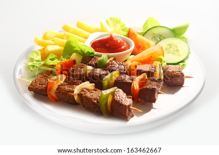 Three grilled beef and sweet pepper kebabs served on a plain white plate with french fries, tomato ketchup and mixed salad on a white background - stock photo