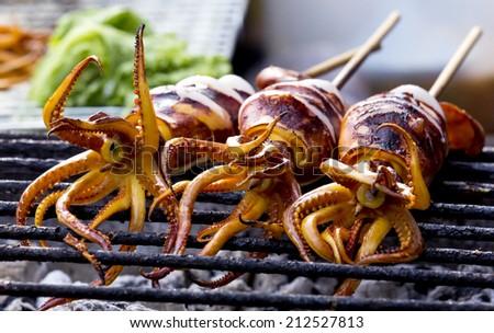 Three Grilled squid on gridiron,Delicious bar b Que sea food. - stock photo