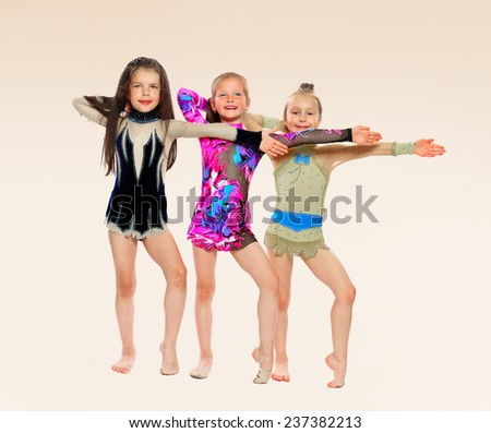 three gymnasts of the girl of 6 years carry out exercises.isolated on white. - stock photo