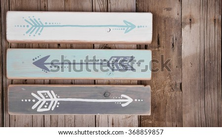 Three hand painted arrows on a wooden plank on a rough wooden background - stock photo