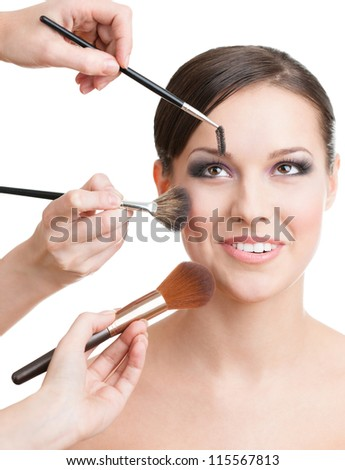 Three hands of makeup artists applying cosmetics on the woman's face with brushes, isolated on white - stock photo
