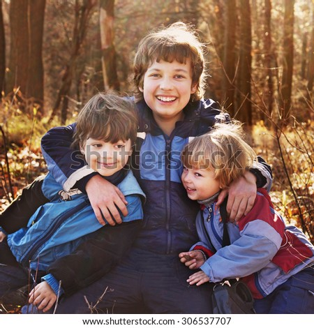 three happy boys  in autumn forest - stock photo