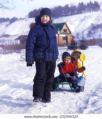 three happy boys on sled play - stock photo