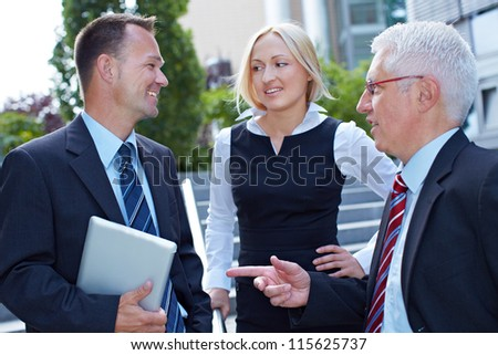 Three happy business people doing small talk outside the office - stock photo
