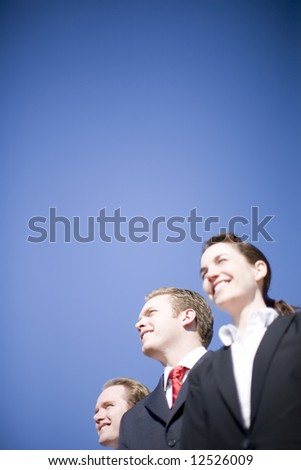 three happy business people looking in same direction wearing suits - stock photo