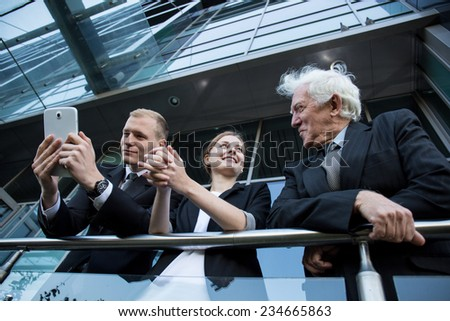 Three happy businesspeople talking on the balocny at break during work - stock photo