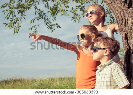 Three happy children  playing near the tree at the day time. Concept Brother And Sister Together Forever - stock photo