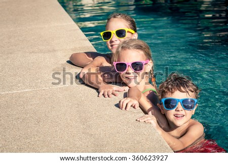 Three happy children  playing on the swimming pool at the day time. Concept of friendly family. - stock photo