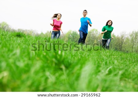 Three happy friends having fun on the spring meadow - stock photo