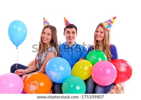 Three happy friends in hats with balloons sitting on the couch - stock photo