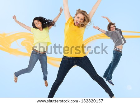 Three happy friends jumping for joy with yellow smoke trail on blue background - stock photo