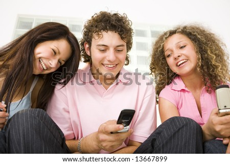 Three happy friends sitting and looking at mobilephone. A boy holding mobile phone. Low angle view. - stock photo