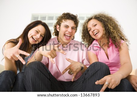 Three happy friends sitting and showing some hands signs. Looking at camera. Low angle view. - stock photo