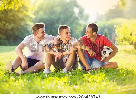 Three happy friends spending free time together in park sitting on grass and chatting - stock photo