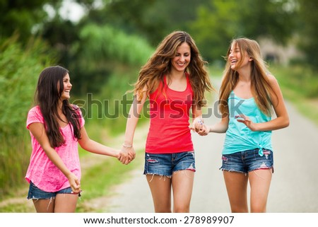 Three happy girls are walking on the road and talking - stock photo