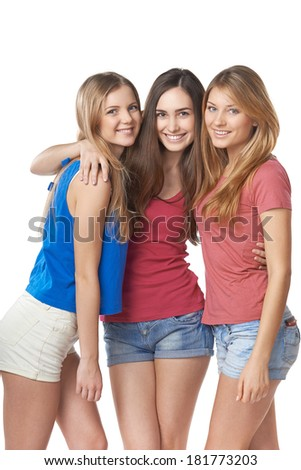Three happy girls friends standing hugging against white background - stock photo