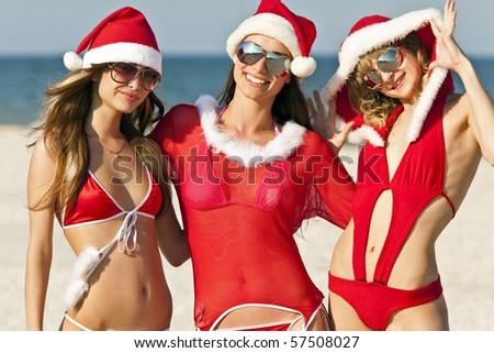 Three happy girls in Santa Clause suit having fun on the beach - stock photo