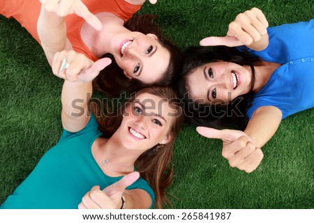 Three happy girls smiling lying on the grass showing thumb up - stock photo